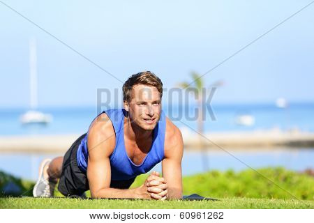 Plank core exercise. Fitness man training working out his midsection core muscles. Fit male fitness instructor planking exercising outside in summer on grass.