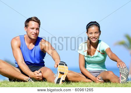 Stretching exercises - Fitness couple outside doing stretches exercise. Fit woman and man doing hamstring leg stretching training in summer. Beautiful multiracial couple.