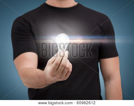 electricity and energy concept - close up of man holding light bulb