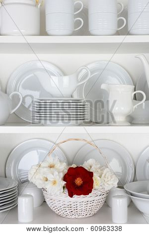 Vertical closeup of a  basket of roses on the shelf of a cupboard full of white plates. Items include, plates, saucers, bowls and a gravy boat. There is one red rose amongst all the white.