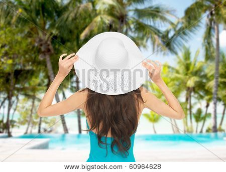 summer and holiday concept - model in swimsuit with hat