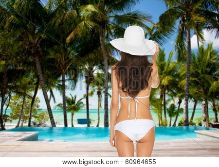 vacation and summer concept - model posing in white bikini with hat