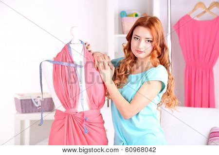 Young girl fashion designer creates new dress in workroom