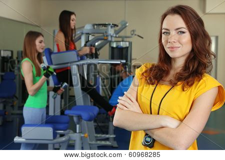Young trainer and womans engaged in simulator in gym