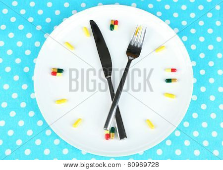 Medication schedule and meals. Conceptual photo. On color napkin background