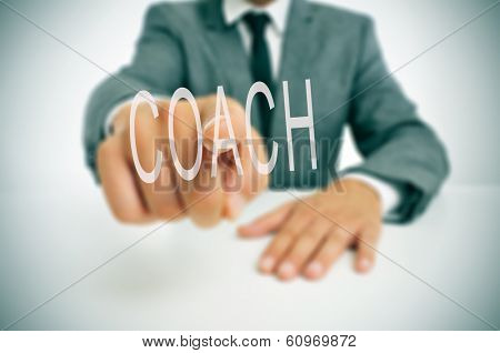 businessman sitting in a desk pointing the word coach written in the foreground