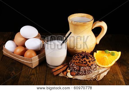 Eggnog with milk and eggs on table and black background