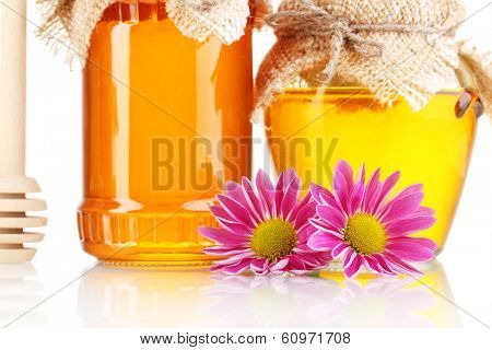 Sweet honey in jars with drizzler close-up isolated on white