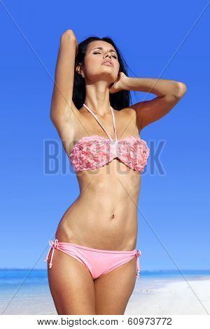 beautiful woman sunbathing in pink bathing suit on beach