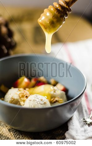 Apple sauce dripping from a wooden dipper in bowl of yogurt; cut fruits and nuts