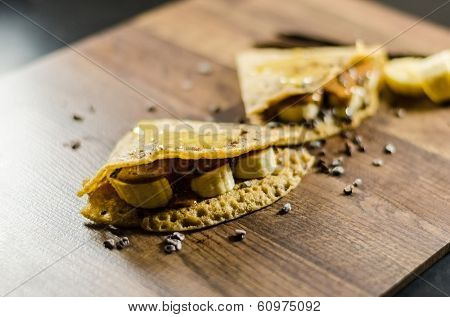 Banana pancakes with choco chips on wooden table
