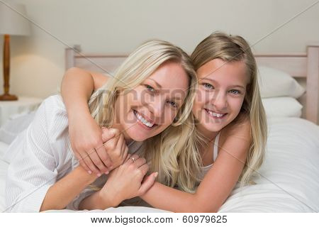 Portrait of loving mother and daughter lying in bed at home