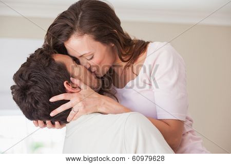 Side view of a loving young couple kissing at home