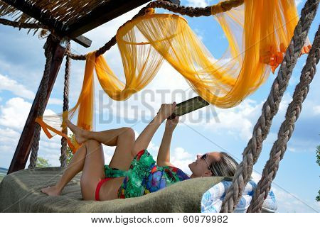 young woman relaxing in hammock using tablet