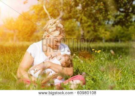 Mother breastfeeding her baby on a great sunny day in a meadow