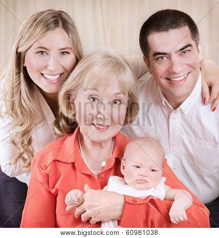 Family generation portrait, beautiful elegant grand mother holding on hands newborn granddaughter, mother and father standing behind them