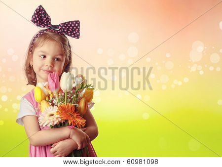 Little girl wih wreath with bow on head holding spring flowers bouquet for the mother's day picture.