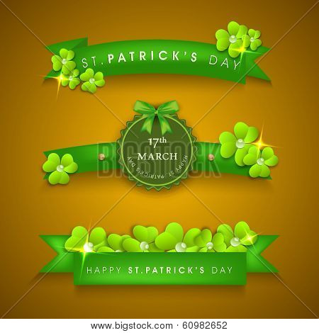 Happy St. Patrick's Day celebrations concept with ribbon, tag or label decorated by shamrock leaves on brown background.