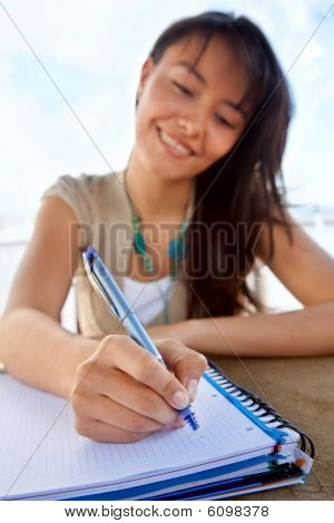 Female Writing On A Notebook