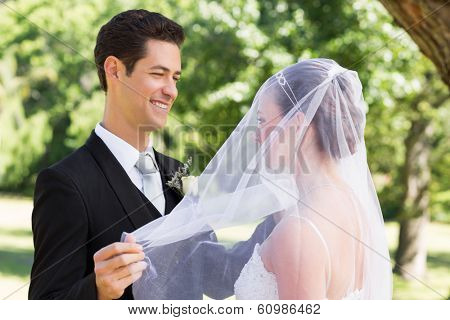 Happy young groom unveiling his bride in garden