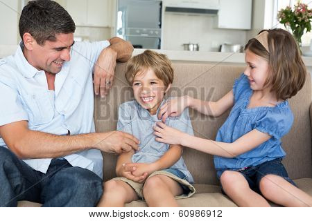 Father and daughter tickling boy sitting on sofa at home