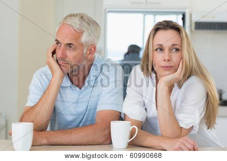 Bored couple sitting at the counter at home in the kitchen
