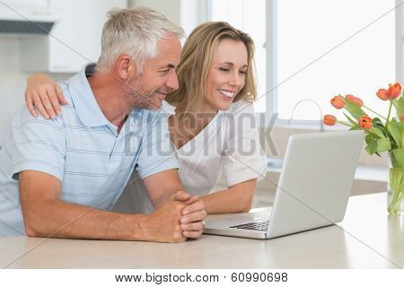 Cheerful couple using laptop together at the worktop at home in the kitchen