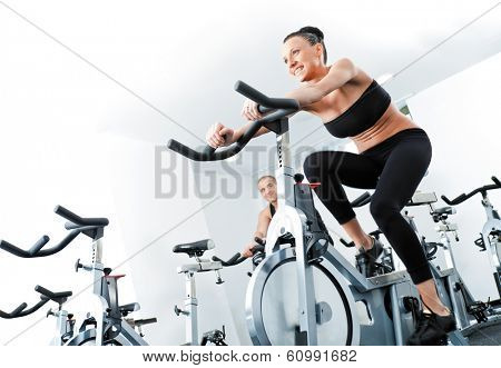 Young athletic female veloargometers in gym, male behind