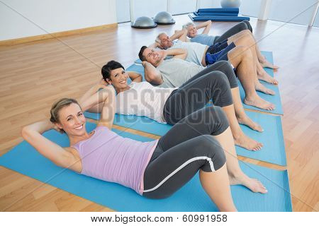 Side view portrait of fitness class lying on mats in row at yoga class