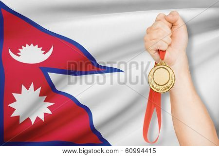 Medal In Hand With Flag On Background - Federal Democratic Republic Of Nepal