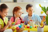 Preschoolers decorating Easter eggs, focus on happy little girl