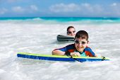 stock photo of boogie board  - Mother and son surfing on boogie boards - JPG