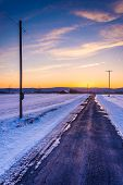 Sunset Over A Country Road Through Snow Covered Fields In Rural Frederick County, Maryland. poster