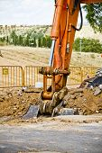 stock photo of risen  - Loader Excavator standing in sandpit with risen bucket over cloudscape sky - JPG