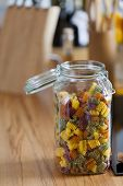 Open Storage Jar With Colorful Pasta On Worktop