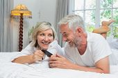 Close-up of a cheerful mature couple reading text message at home