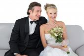 Portrait of happy bride sitting with groom on sofa over white background