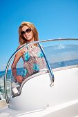 Summer vacation - young girl driving a motor boat