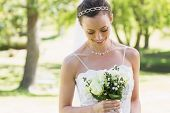 Shy young bride looking at flower bouquet in garden