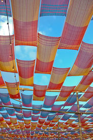 stock photo of canopy roof  - deco colorful fabric canopy roof outdoor on cloudy sky background  - JPG