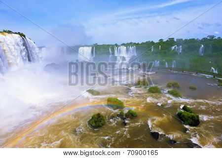 White whipped foam of water and a thin mist over the water.  Magnificent rainbow shines in the mist. The most high-water waterfall in the world - Iguazu. The Brazilian side of the park.