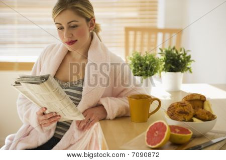 Female With Breakfast And Newspaper In Kitchen