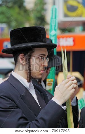 BNEI BRAK, ISRAEL- SEPTEMBER 22, 2010:  The young religious Jews in hat are choosing ritual plants at the market on the eve of Sukkot. This was Sukkoth market