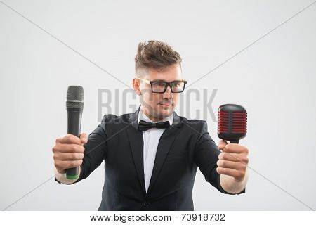 DJ in tuxedo posing with two microphones