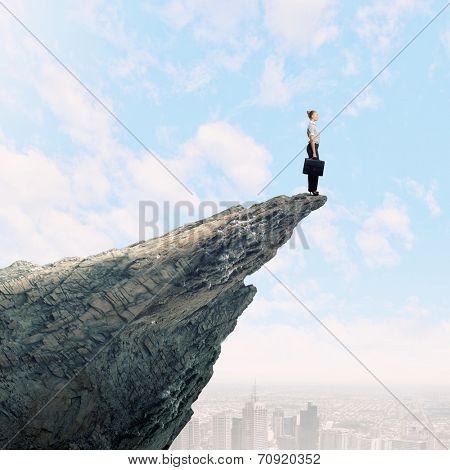 Risky businesswoman standing on edge of rock