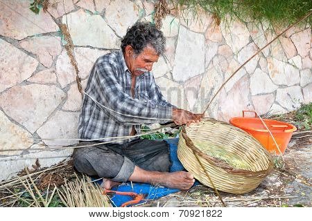 PARGA, GREECE-MAY 28, 2014: Unidentified man maging wicker Basket on May 28, 2014. in Parga, Greece.