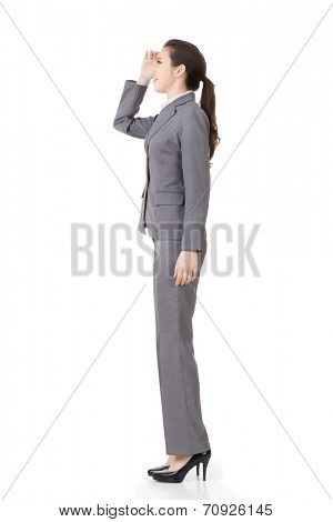Side view of Asian businesswoman looking far away, full length portrait isolated on white background.