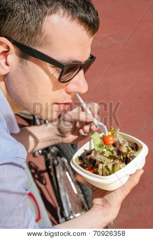Young business man eating at lunch break outdoors