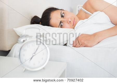 Beautiful young woman looking at alarm clock on bedside table at home