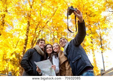 travel, people, tourism, technology and friendship concept - group of smiling friends with map and camera making self portrait in city park